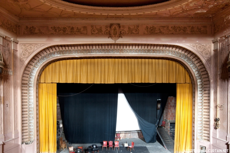The Proscenium arch is surrounded by beaded plaster molding and a motif of acanthus leaves. At the center is the figure of a girl that is repeated throughout the plaster-work of the theater.