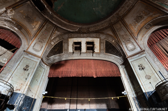 The proscenium has two large holes in it due to the removal of sound or lighting equipment after the theater closed.