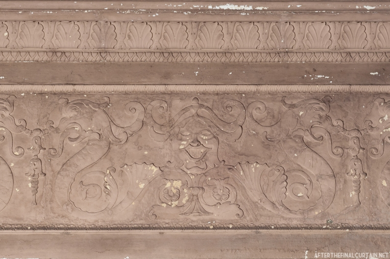 A face in plaster-work above the balcony.