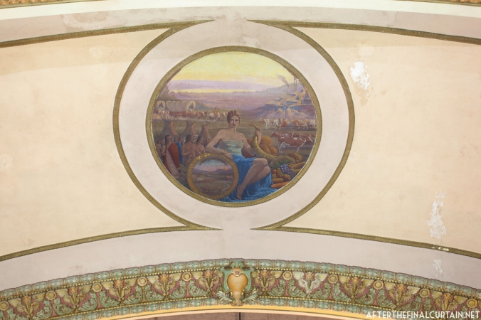 The mural on the proscenium depicts Demeter, the greek goddess of agriculture surrounded by symbols of Kansas' history including the state seal of Kansas.