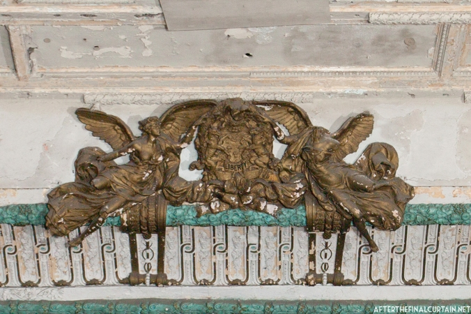 The plasterwork at the top of the proscenium arch depicts two angels surrounding the state seal of Pennsylvania. In the center is the word Liberty, part of the state's motto.