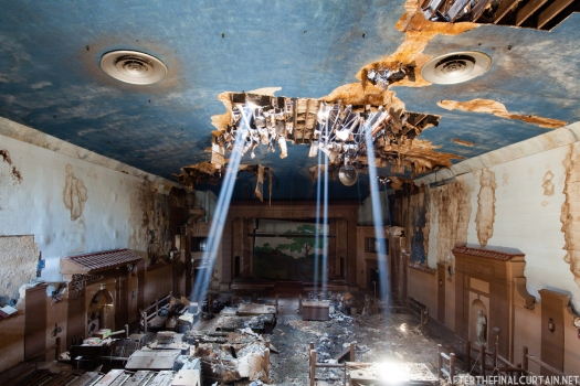 Sunlight pours in through holes in the ceiling, due to years of water damage.